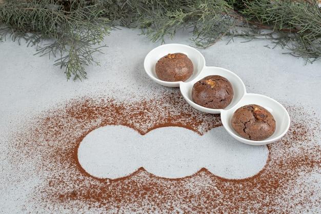 Białe talerze z czekoladowymi ciasteczkami ze sproszkowanym kakao.