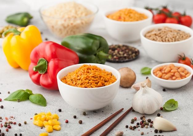 Białe talerze z gotowanym ryżem basmati długoziarnistym z warzywami i grzybami na jasnym tle z patyczkami i papryką paprykową z kukurydzą, czosnkiem i bazylią z fasolą i groszkiem.