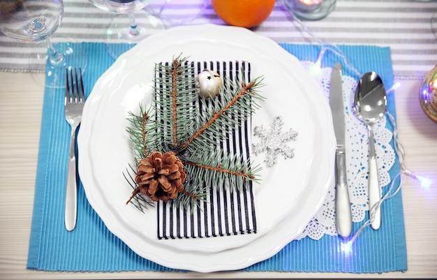 Białe talerze ze sztućcami na świątecznym stole, z bliska close