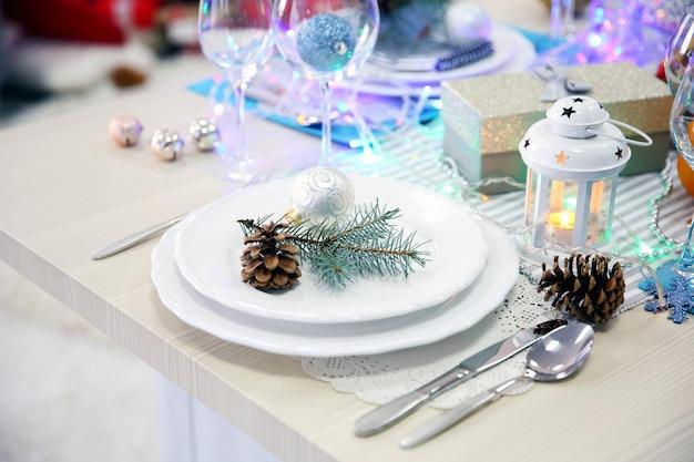 Białe talerze ze sztućcami na świątecznym stole