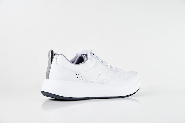 Białe tenisówki męskie na na białym tle. stylowe buty sportowe moda, z bliska