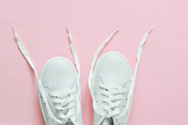 Białe tenisówki na różowym tle z niewiązanymi koronkami