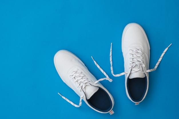 Białe tenisówki z rozwiązanymi sznurówkami na niebieskiej powierzchni