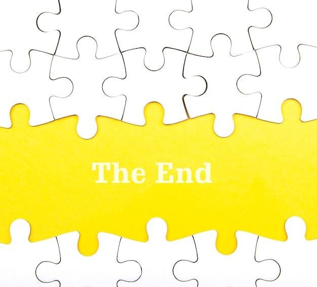 Białe tło układanki z brakującymi elementami. słowa the end na żółtym tle