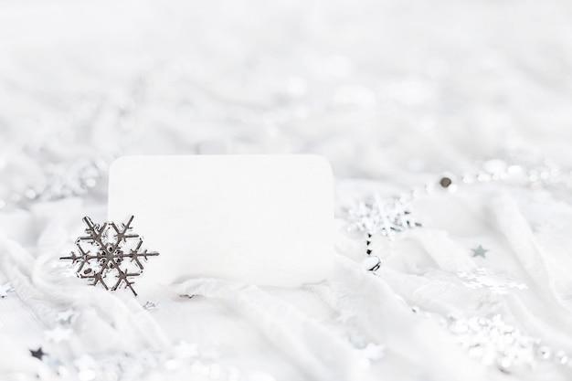 Białe tło wakacje z błyszczącymi srebrnymi płatkami śniegu, ozdób choinkowych i czystym kawałkiem papieru