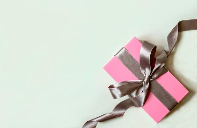 Białe tło z różowym pudełkiem i srebrną wstążką