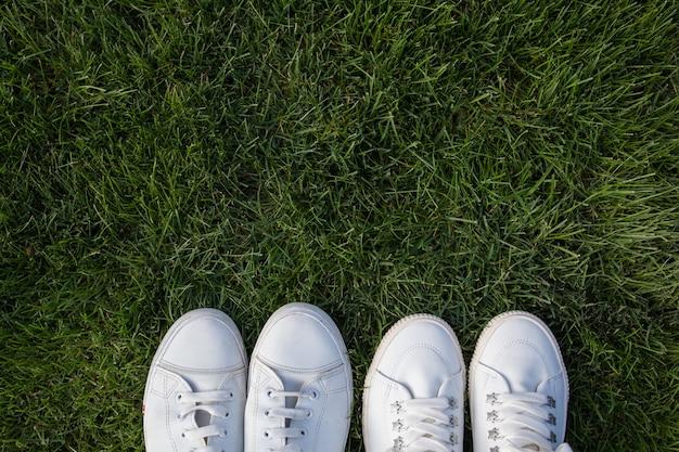 Białe trampki damskie i męskie na zielonej trawie. facet i dziewczyna stoją naprzeciw siebie.
