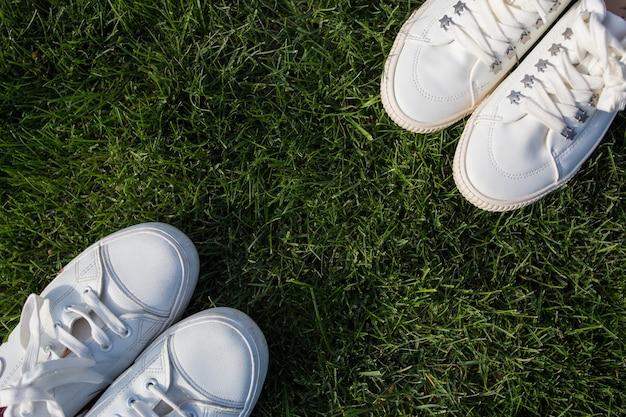 Białe trampki damskie i męskie na zielonej trawie. facet i dziewczyna stoją naprzeciwko siebie. widok z góry.