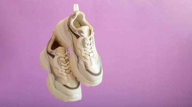 Białe trampki latają na fioletowej ścianie. kobiece białe skórzane buty na fioletowym tle. para stylowych miejskich trampek. wygodne sportowe buty damskie hipster. długi baner internetowy z miejsca na kopię.