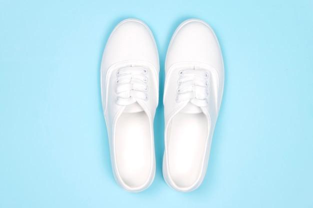 Białe trampki na niebieskim tle, płaskie, modne buty,