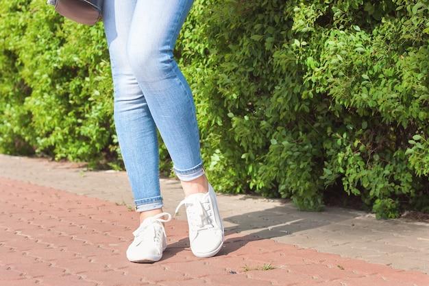 Białe trampki na nogach kobiet w dżinsach na asfalcie i zielonym tle roślin.