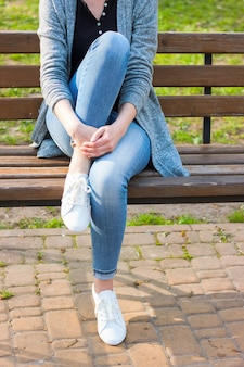 Białe trampki na nogach kobiet w dżinsach na niebieskiej ławce i zielonym tle roślin.