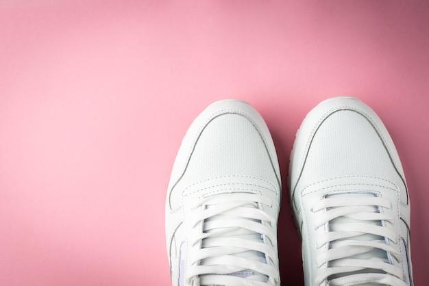 Białe trampki na różowym tle.