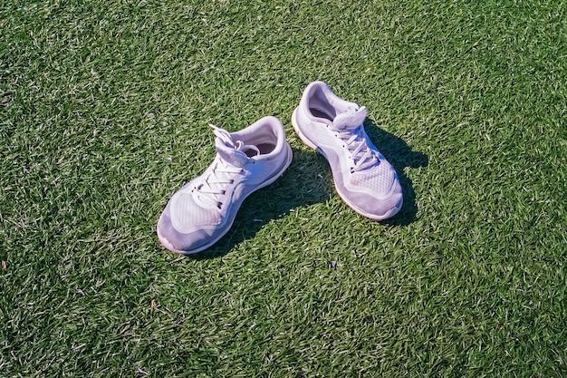 Białe trampki na zielonej trawie. przestrzeń do użytku redakcyjnego.