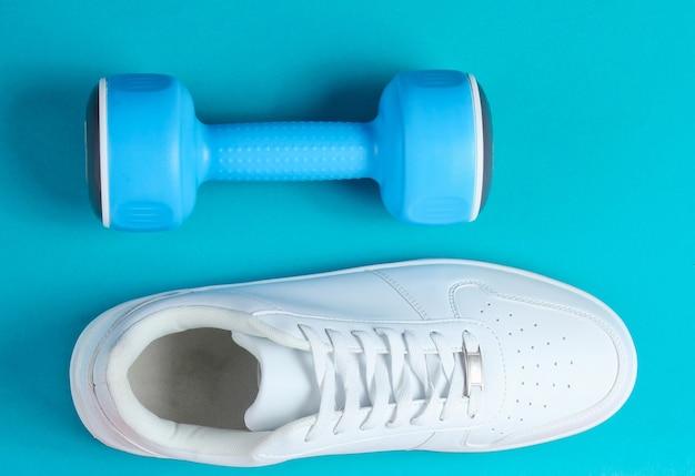 Białe trampki, plastikowe hantle na dwukolorowym tle. koncepcja sportu. widok z góry