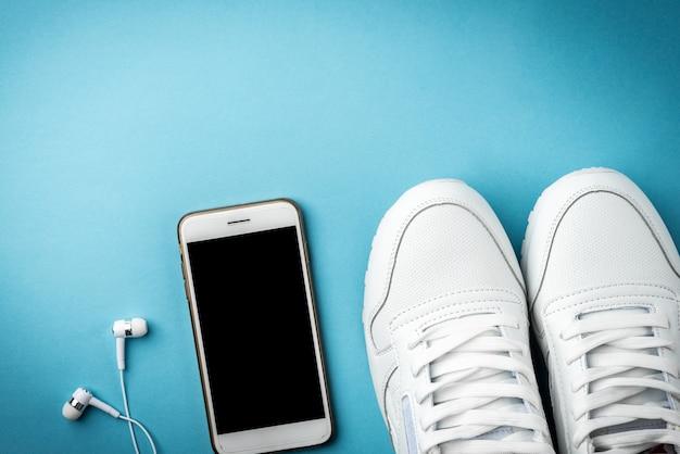 Białe trampki, telefon komórkowy i słuchawki na niebieskiej powierzchni.