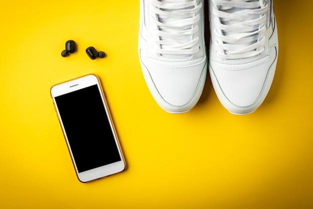 Białe trampki, telefon komórkowy i słuchawki na żółtej powierzchni.