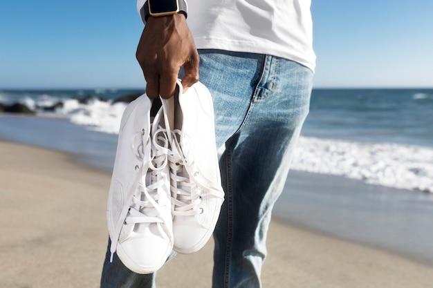 Białe trampki zbliżenie odzież męska letnia sesja zdjęciowa mody na plaży