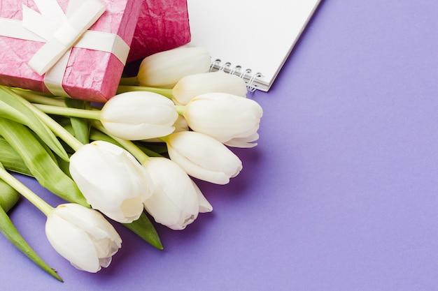 Białe tulipanowe kwiaty i różowo zapakowane prezenty