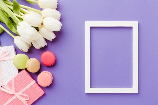Białe tulipany i prezenty z pustą ramką
