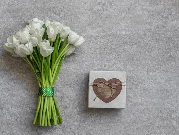 Białe tulipany i pudełko na tle. koncepcja wiosny.