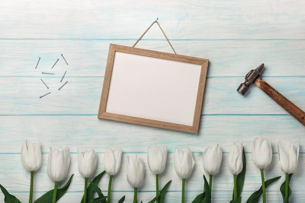 Białe tulipany, kreda, młotek i metalowe gwoździe na niebieskich deskach. dzień matki