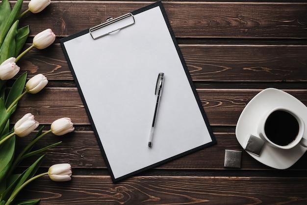 Białe tulipany na drewnianym stole z pustą papierową tabletką i filiżanką kawy