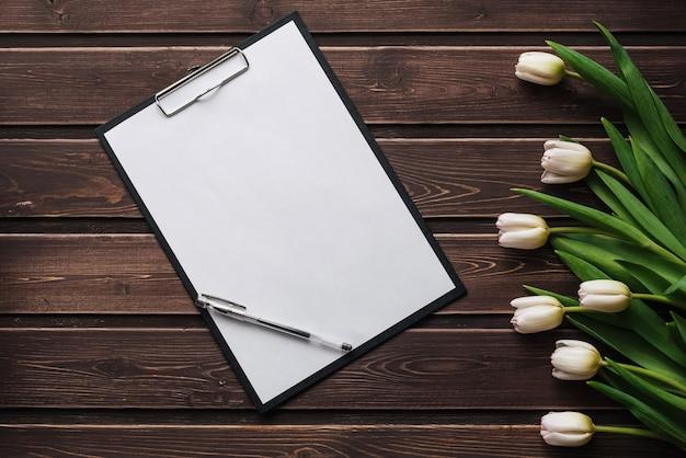Białe tulipany na drewnianym stole z pustą papierową tabletką. puste kartkę z życzeniami na walentynki