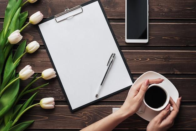 Białe tulipany na drewnianym stole z pustym papierem, smartfonem i filiżanką kawy