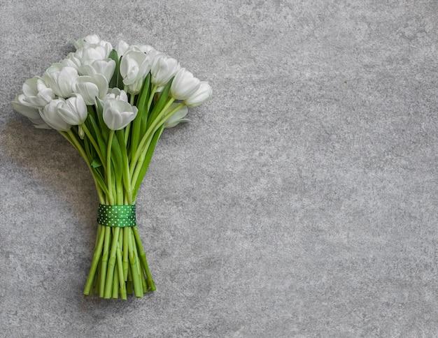 Białe tulipany na niebieskim tle. koncepcja wiosny.