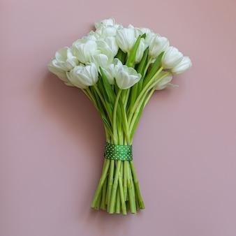 Białe tulipany na różowym tle. koncepcja wiosny.