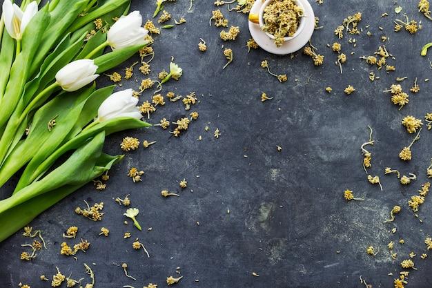 Białe tulipany z suszonymi kwiatami w filiżance na czarnej powierzchni