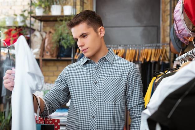 Białe ubrania. spokojny, poważny młody człowiek przyglądający się uważnie białej koszulce w ręku i myślący o zakupie