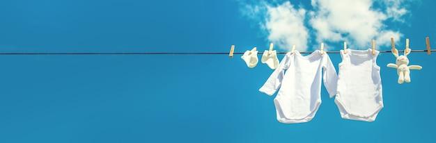 Białe ubranka dla niemowląt wysychają na linie