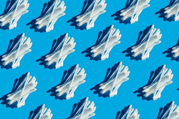 Białe waciki leżą w rzędzie na niebieskim tle wzór