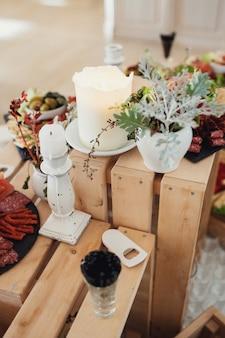 Białe wazony z zielenią stoją na drewnianych pudełkach