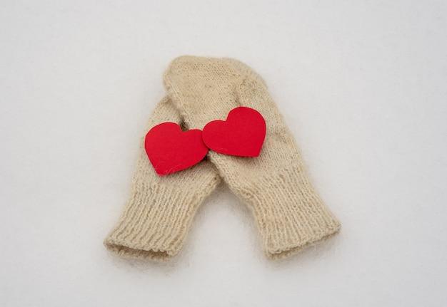 Białe wełniane rękawiczki damskie na białym śniegu. ubrania zimowe. dwa czerwone serca. walentynki.