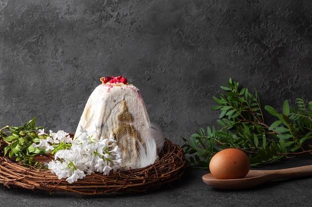 Białe wielkanocne ciasto kulich, brązowe jajko i liście