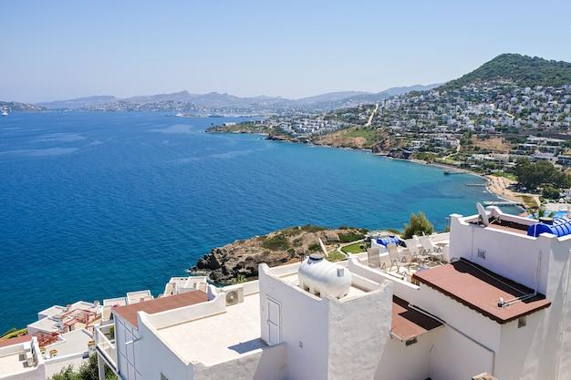Białe wille wakacyjne w ośrodku z widokiem na morze, palmy i miasto.