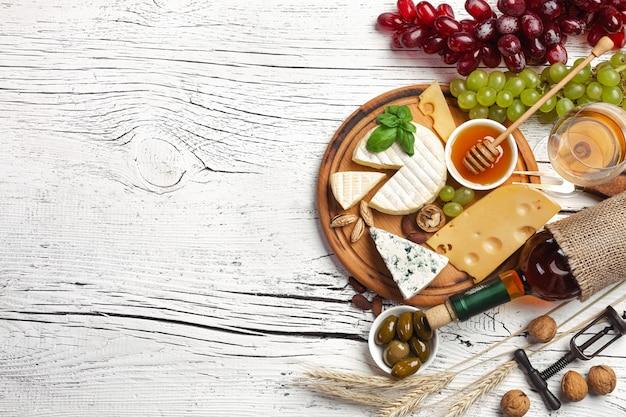 Białe wino butelka, winogrono, miód, ser i lampka na białym drewnianym tle
