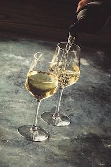 Białe wino leje do szklanek, z bliska