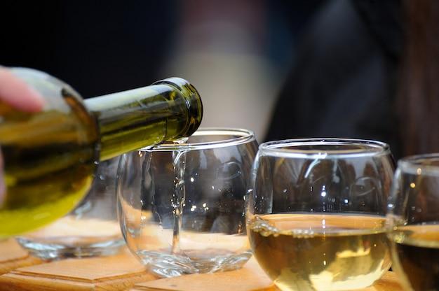 Białe wino nalewane z butelki do kieliszka