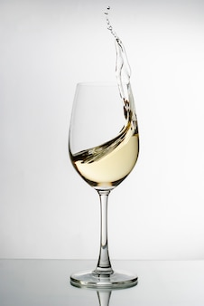 Białe wino pluskające z eleganckiego kieliszka