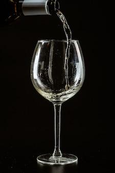 Białe wino przelewa się do ciemnego kieliszka do wina