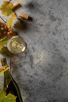 Białe wino w kieliszku, winogrona i gałęzie winogron na stole. widok z góry. skopiuj miejsce na tekst.