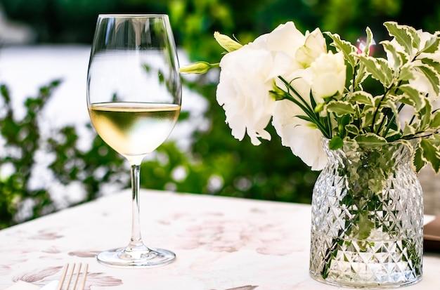 Białe wino w luksusowej restauracji na letnim tarasie w ogrodzie degustacja wina w winnicy w vi...