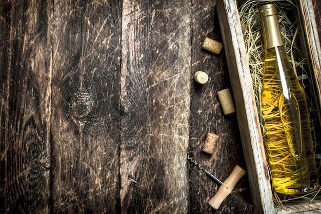 Białe wino w starym pudełku z zielonymi winogronami. na drewnianym tle.