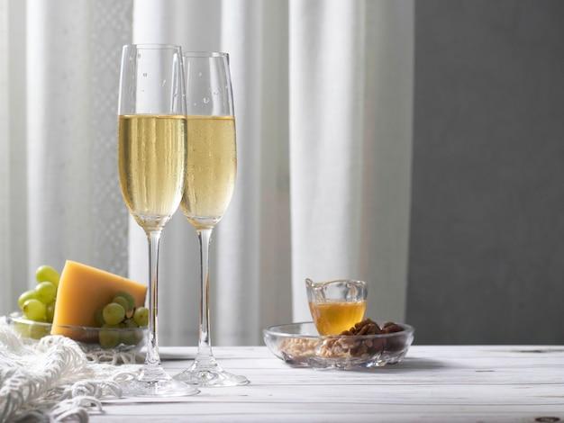 Białe wino w wysokich kieliszkach i przystawka z serem, winogronami, miodem i orzechami