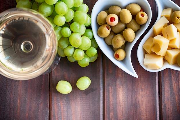 Białe wino, winogrono, oliwki i ser na stole woden