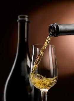 Białe wino wlewa się do kieliszka